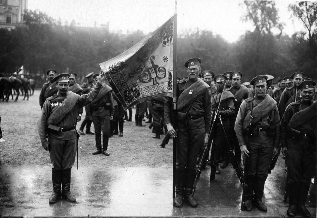 """Le drapeau du 2e régiment de la 1ère brigade spéciale russe près des Champs-Élysées avant le défilé du 14 juillet 1916. On reconnaît au centre du drapeau le monogramme impérial """"H II"""" pour Nicolas II. Le porte-drapeau du régiment   se nomme Vassili Sablitzeff. Collection Andreï Korliakov (France)"""
